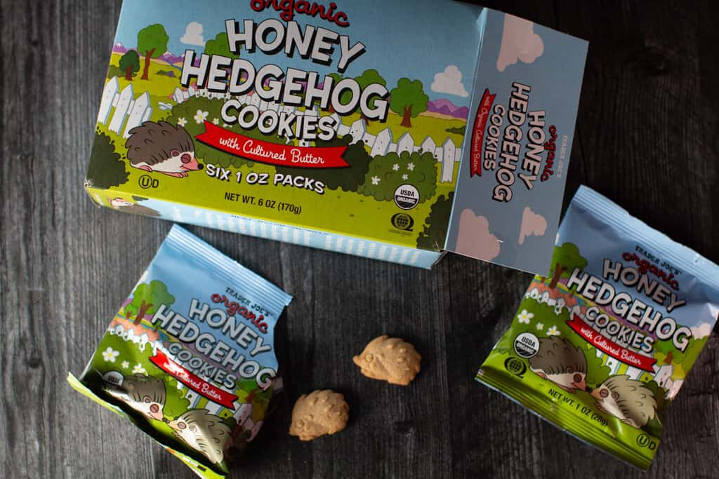 The open box of Trader Joe's Organic Honey Hedgehog Cookies showing an unopen bag and one open bag with a few crackers out of the bag.