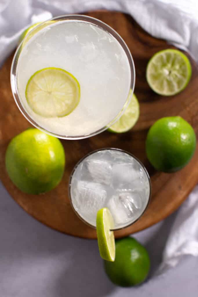 Two vodka gimlets garnished with lime. One is served in martini glass, the other in a rocks glass with ice.