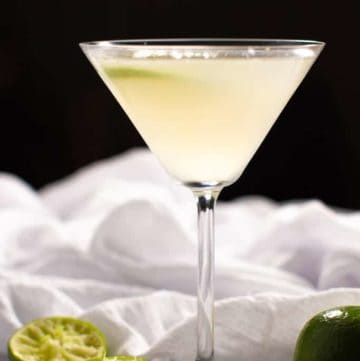 A vodka gimlet served in a martini glass garnished with a lime wedge and surrounded by a white cloth and squeezed limes