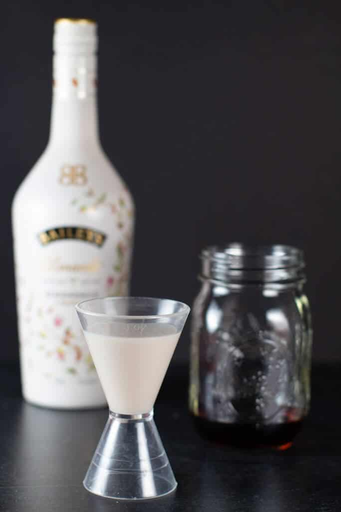 A measuring cup with the Bailey's Almande for the nuts and berries cocktail with the original bottle in the background