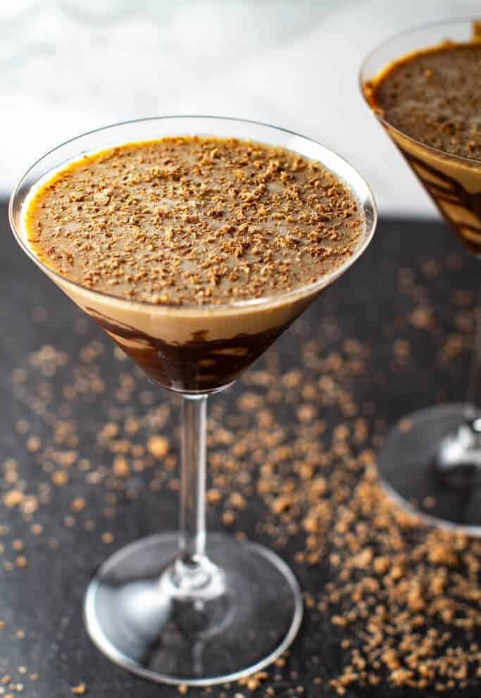 A close up of two chocolate martinis with chocolate shavings on the black surface