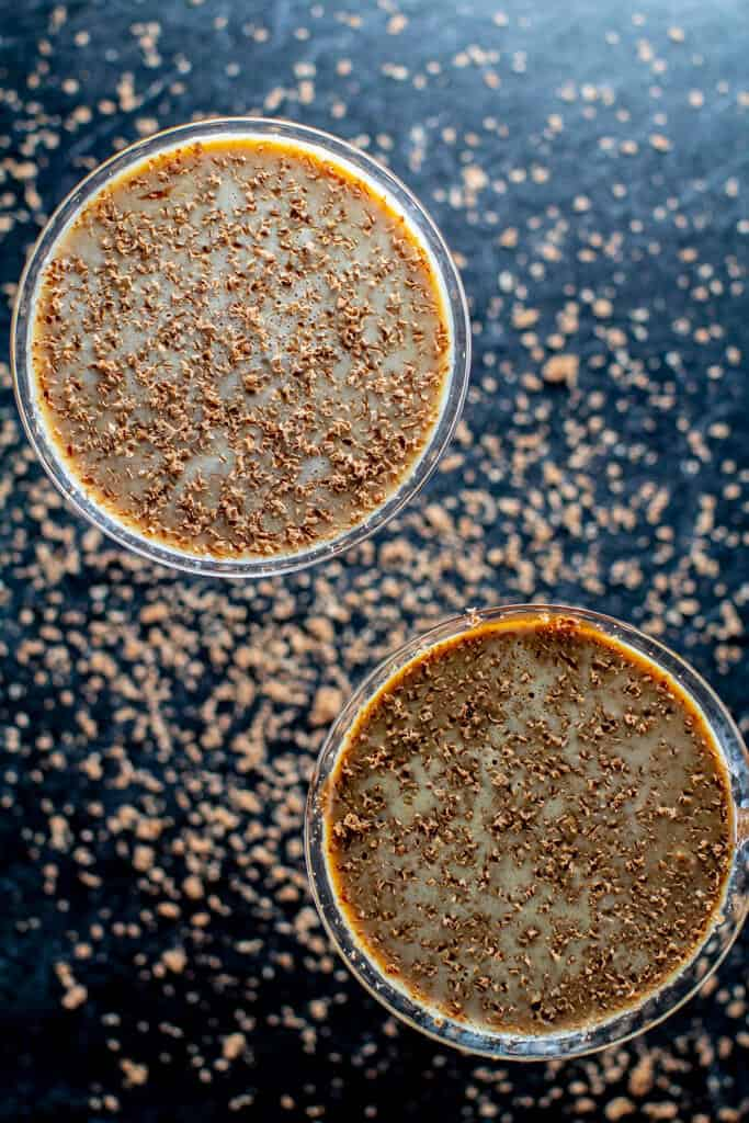 An overhead shot of two chocolate martinis on the black surface surrounded by chocolate shavings