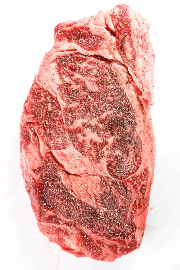 A seasoned ribeye steak with salt and pepper.