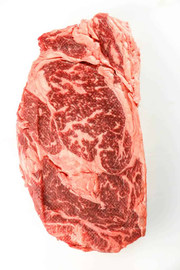 A Ribeye Steak Showing Marbling on a white surface