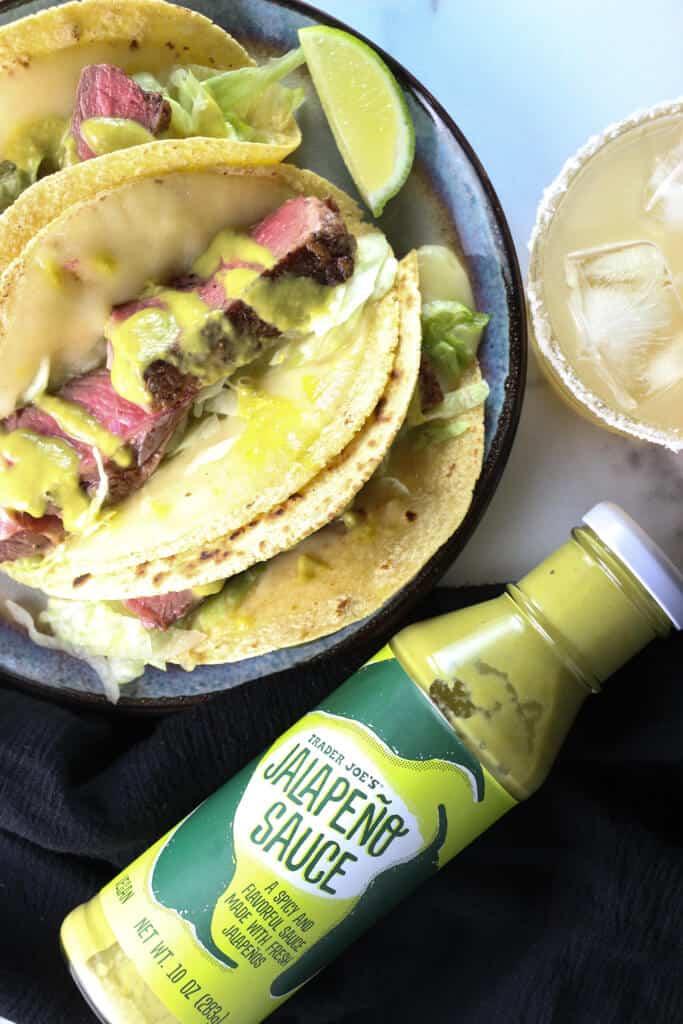 A jar of Trader Joe's Jalapeno Sauce next to Ribeye Tacos and a Cadillac Margarita