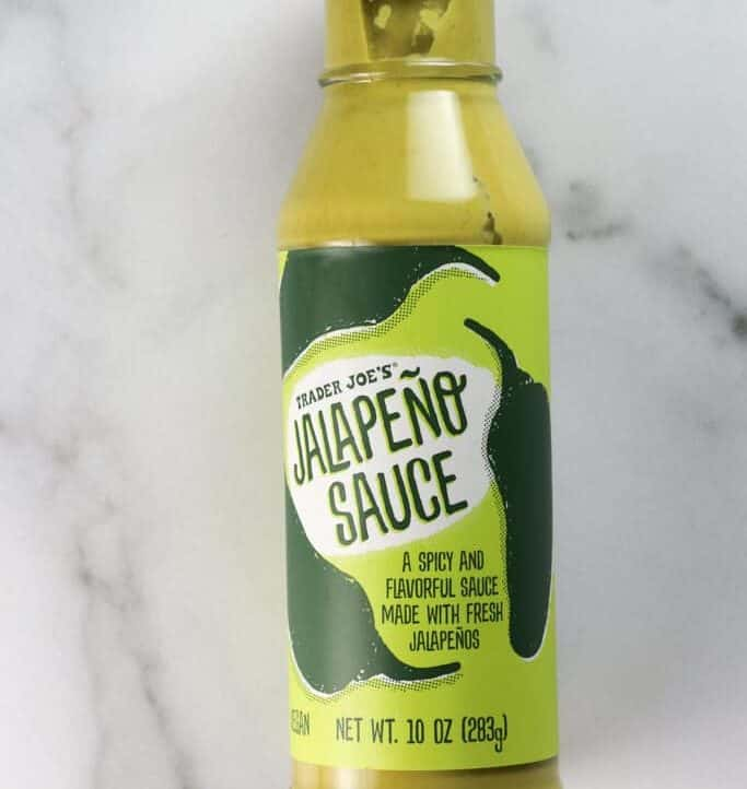 An unopened bottle of Trader Joe's Jalapeno Sauce on a marble surface