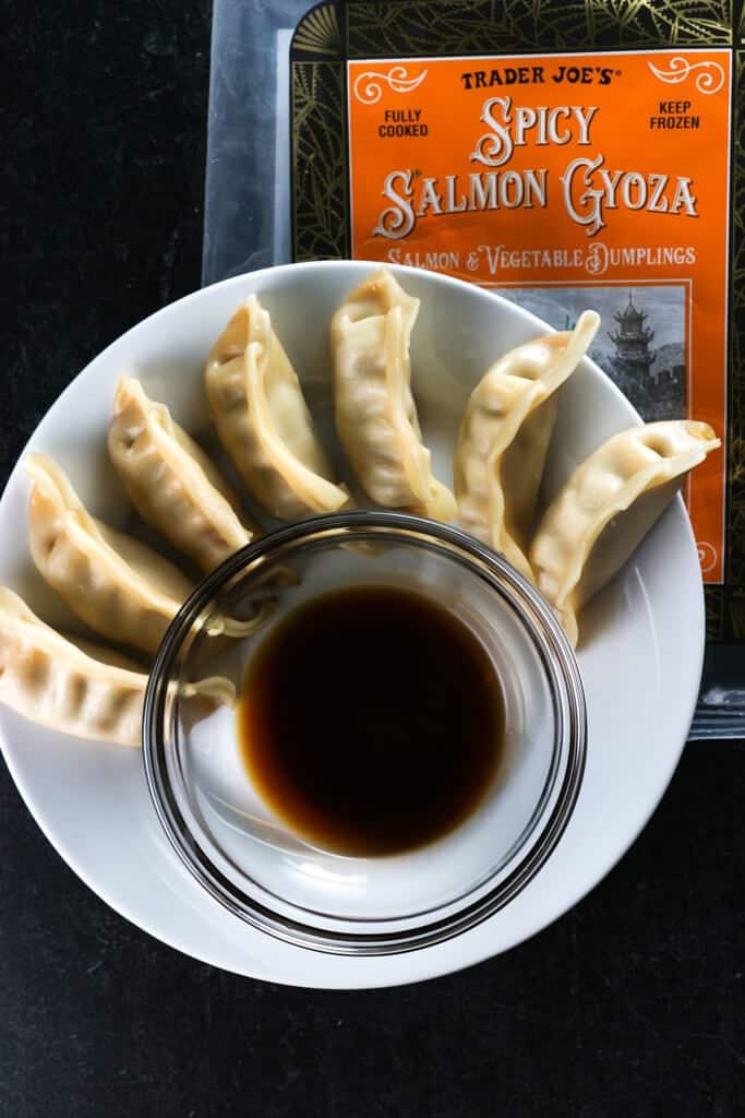 A plate full of Trader Joe's Spicy Salmon Gyoza next to soy sauce and the original bag on a black surface