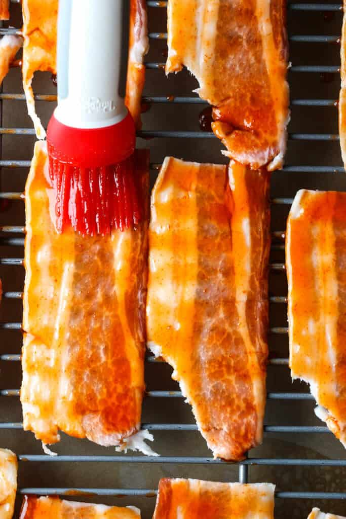 A closeup view of the bacon on a rack being brushed with the sauce with the brush in view