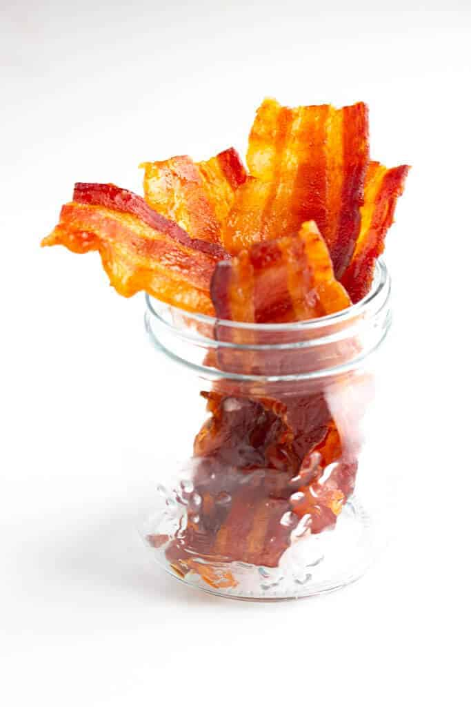 Bacon Jerky in a small mason jar on a white surface