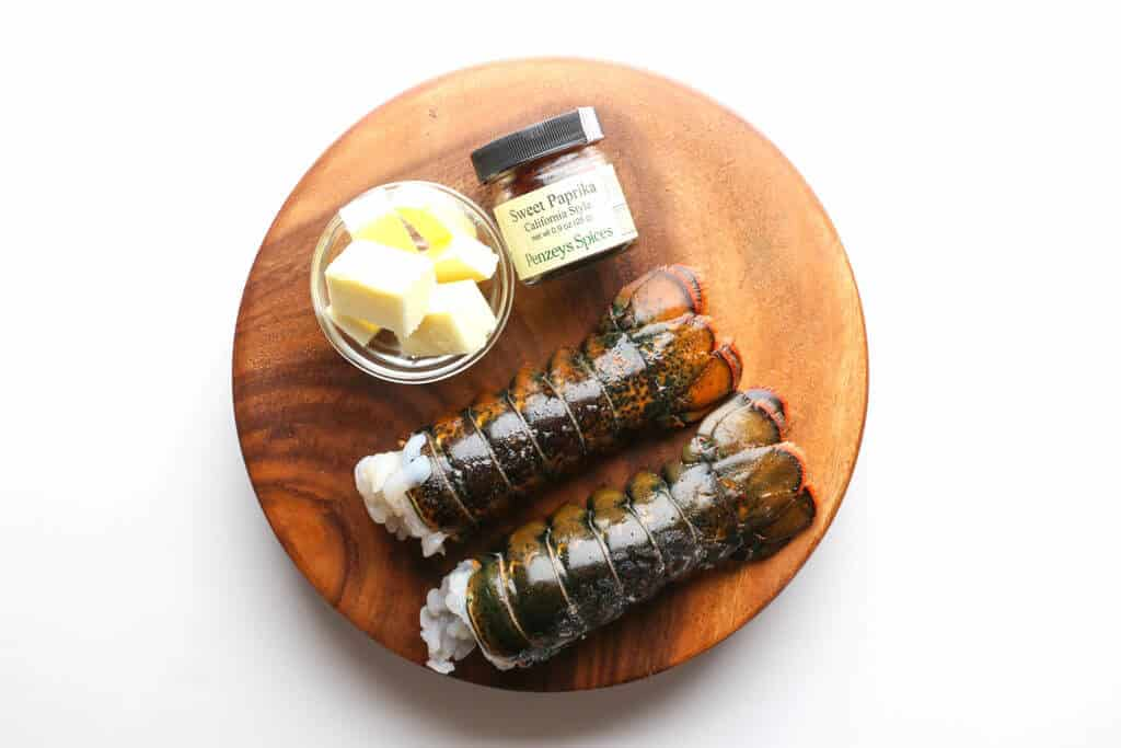 Two lobster tails, butter, and paprika on a round wooden board on a white surface
