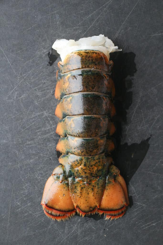 A fully defrosted lobster tail on a black cutting board