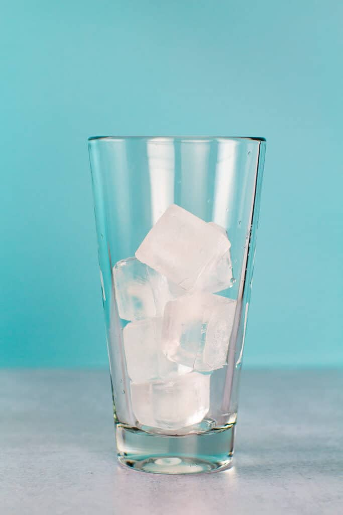 Ice in a shaker glass with an aqua colored background