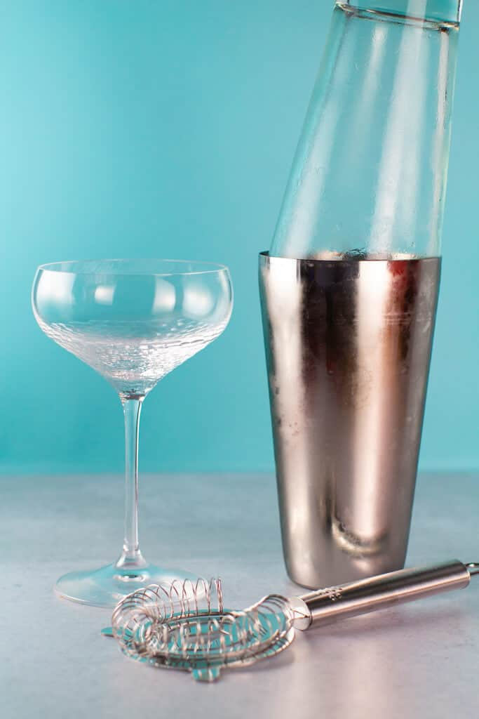 An ice cold shaker with frosted sides next to the cocktail glass and strainer