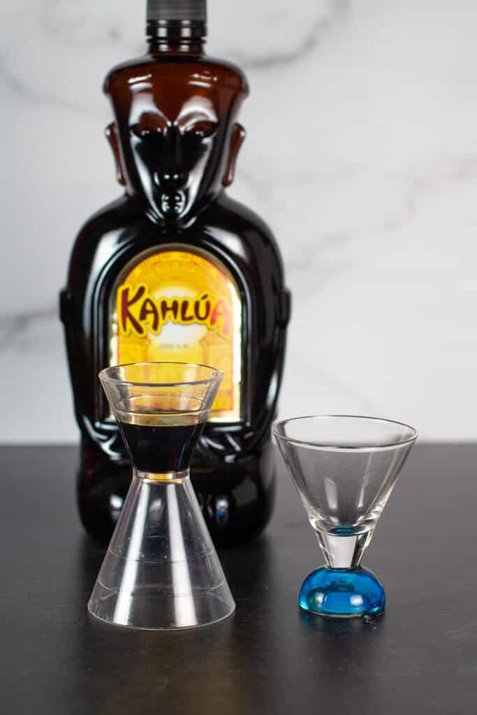 Step 1 of Making a B52 cocktail is adding the Kahlua. Kalua is in a measuring cup next to the final shot glass.