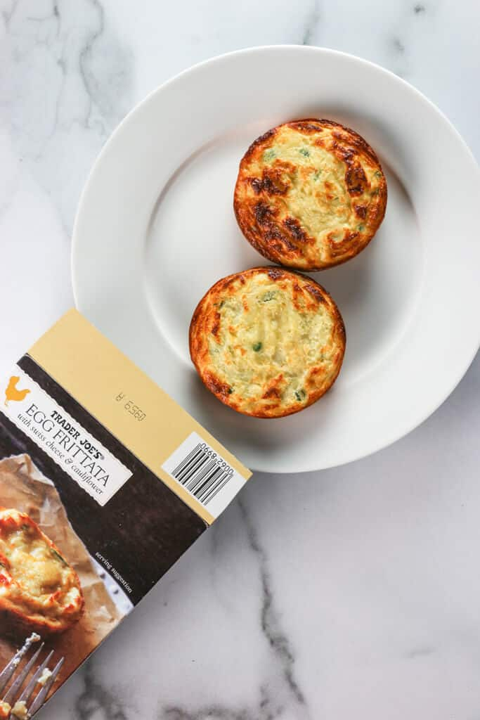Two fully cooked Trader Joe's Egg Frittatas on a white plate next to the original box on a marble surface