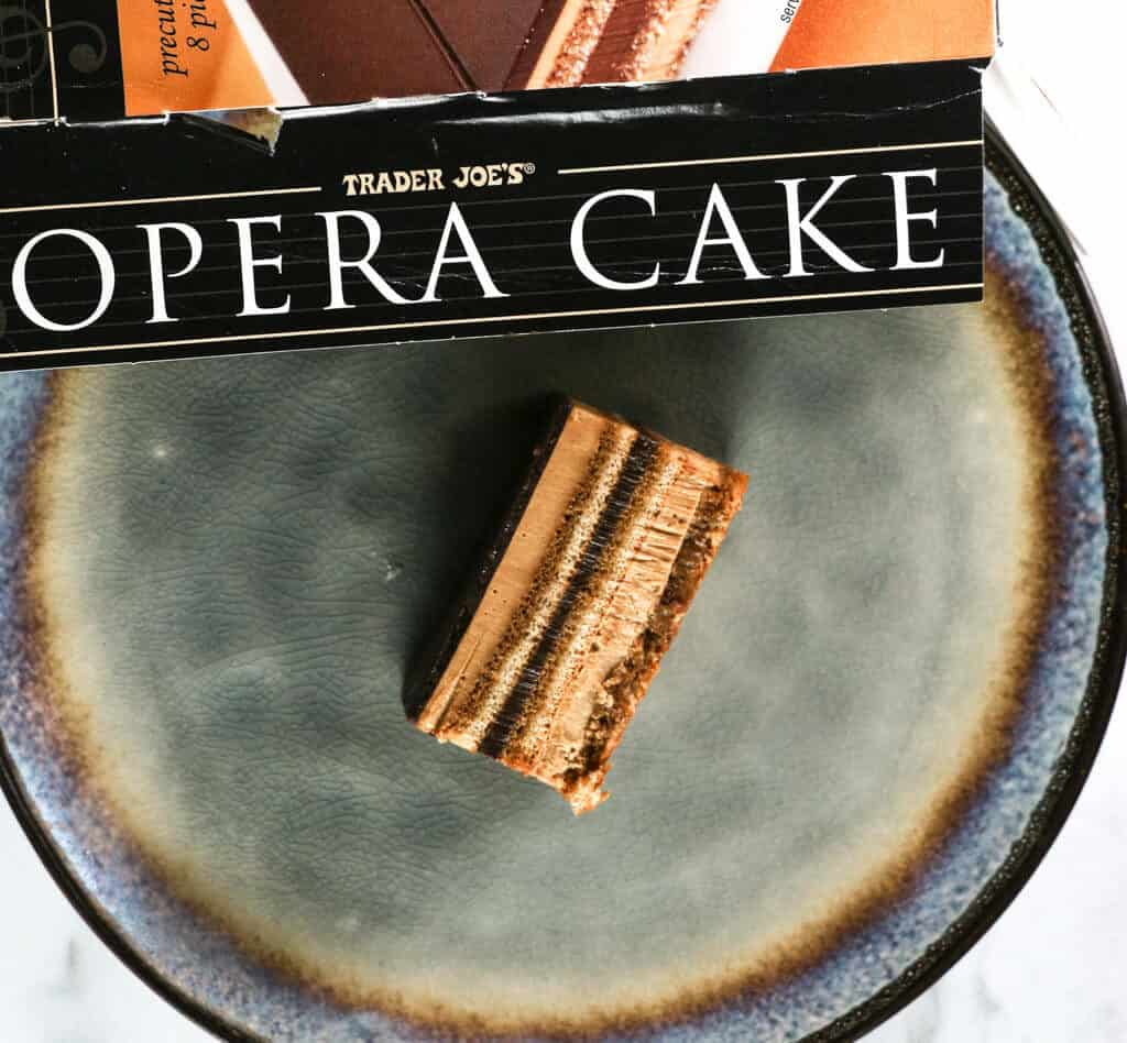 A piece of Trader Joe's Opera Cake on its side showing the layers on a light blue plate