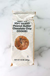 An unopened bag of Trader Joe's Soft Baked Peanut Butter Chocolate Chip Cookies on a marble surface