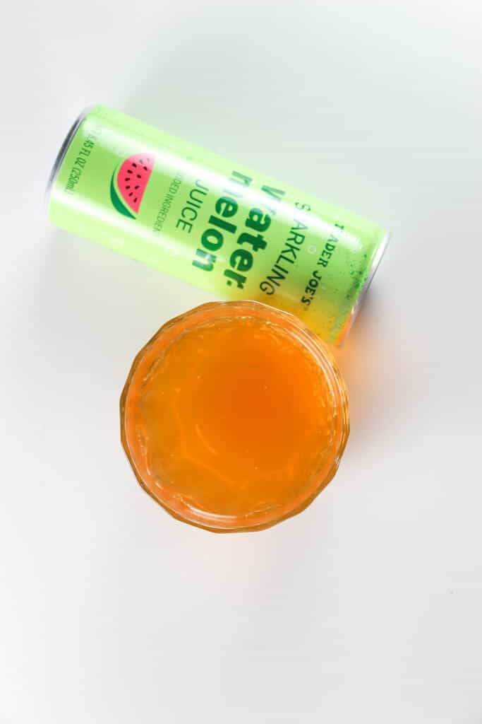An open can of Trader Joe's Sparkling Watermelon Juice showing the orange liquid in a clear cup