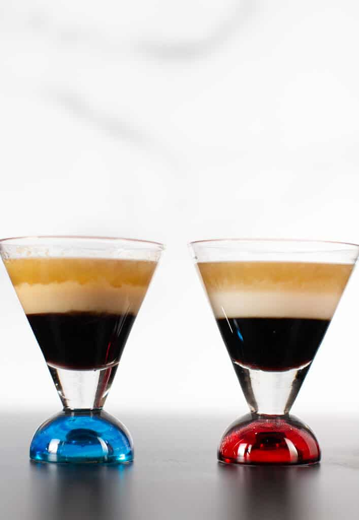 Two B 52 Cocktails side by side. The shot glass with the blue bottom has kahlua, irish cream, and grand marnier. The shot glass on the right with a red bottom is non dairy.