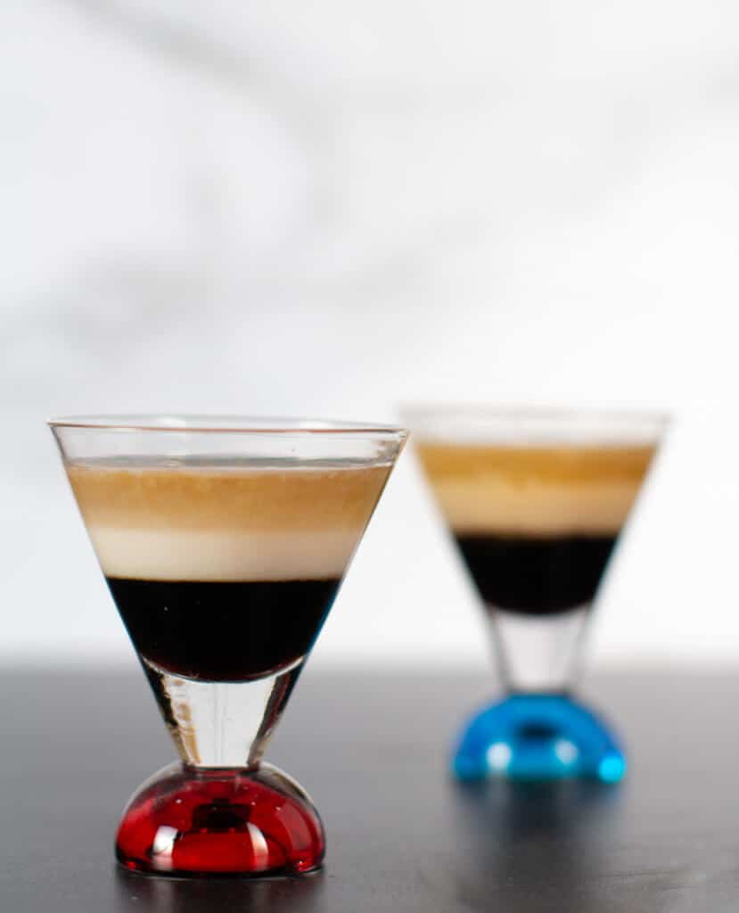Two finished B 52 Cocktails. The shot glass that has a red bottom is the non diary, the shot glass with a blue bottom has the Irish Cream Liqueur