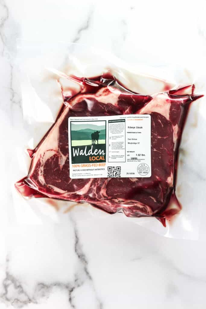 Locally Sourced Riebeye Steaks from Walden Local Farms. Vacuum sealed meat lists farmers name and farm location, contains 2 ribeyes and is placed on a marble surface