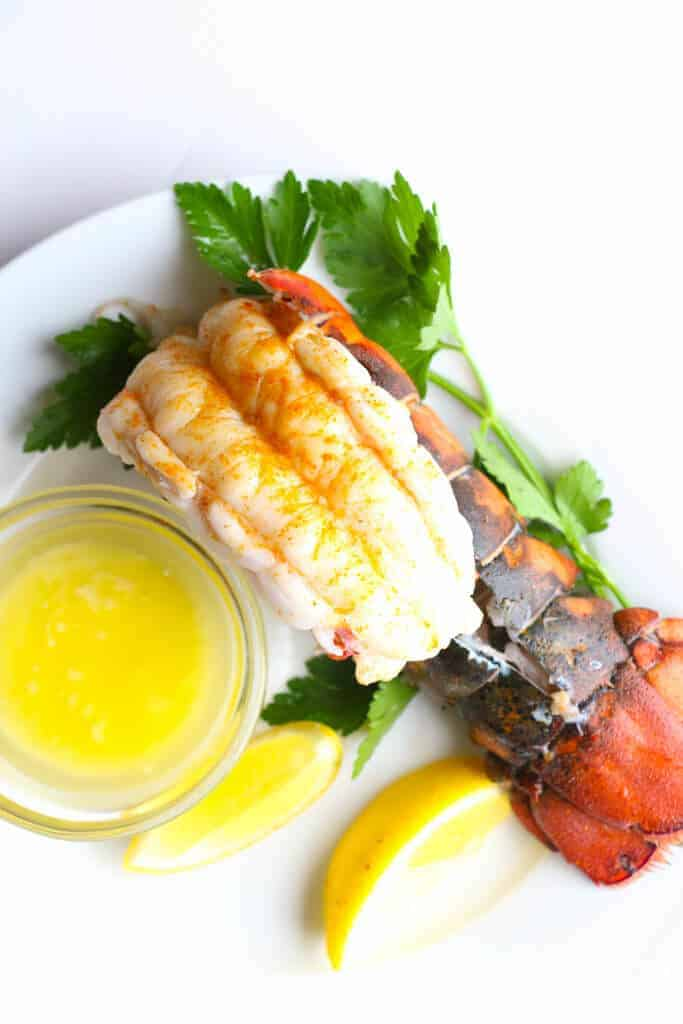 A fully cooked lobster tail with lemon, parsley, and melted butter on a white plate