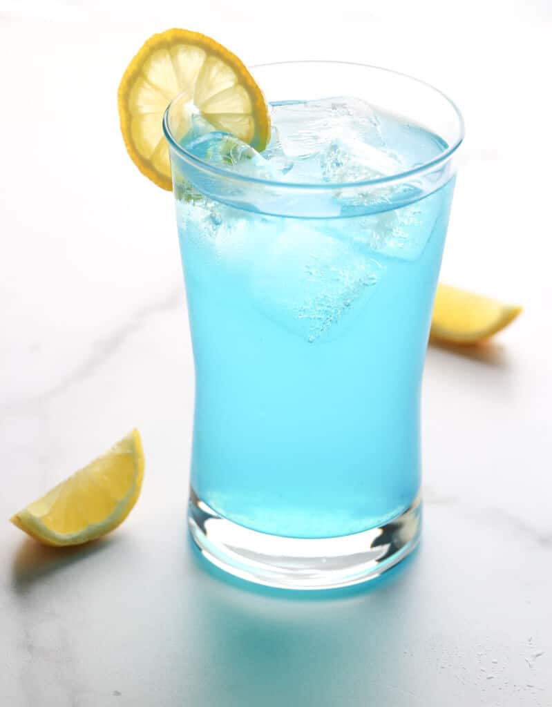 A back lit shot of a finished electric lemonade with two lemon slices around a garnished glass of Electric Lemonade
