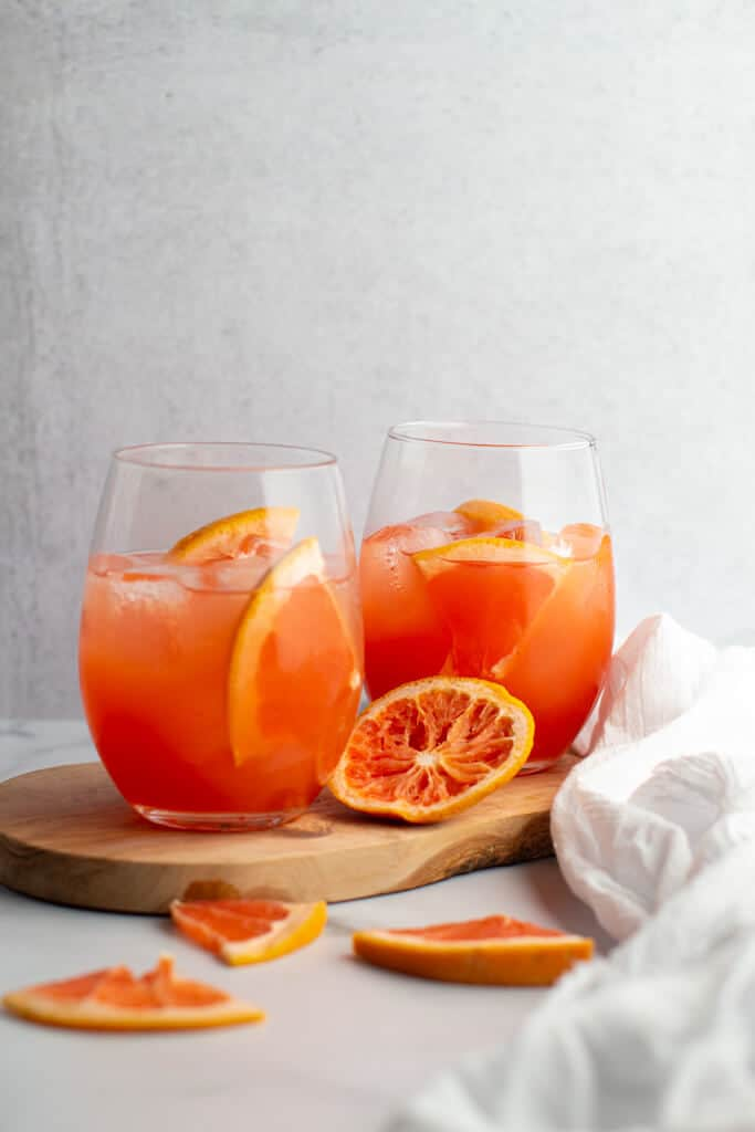 Two finished greyhound cocktails with slices of grapefruit all around and a white cloth draped across the scene