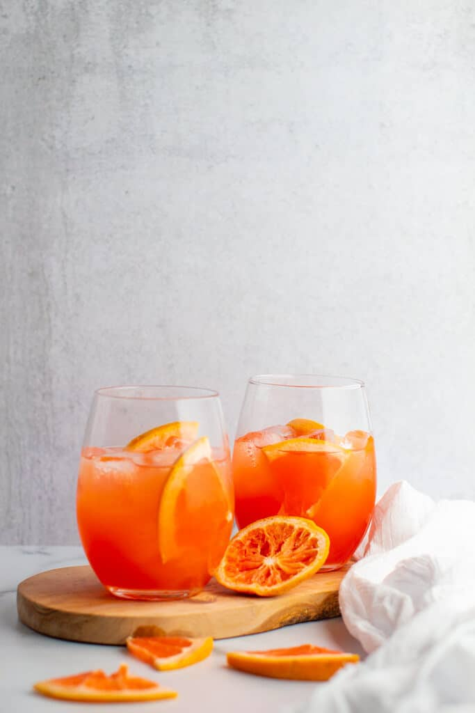 Two finished greyhound cocktails with slices of grapefruit all around zoomed out