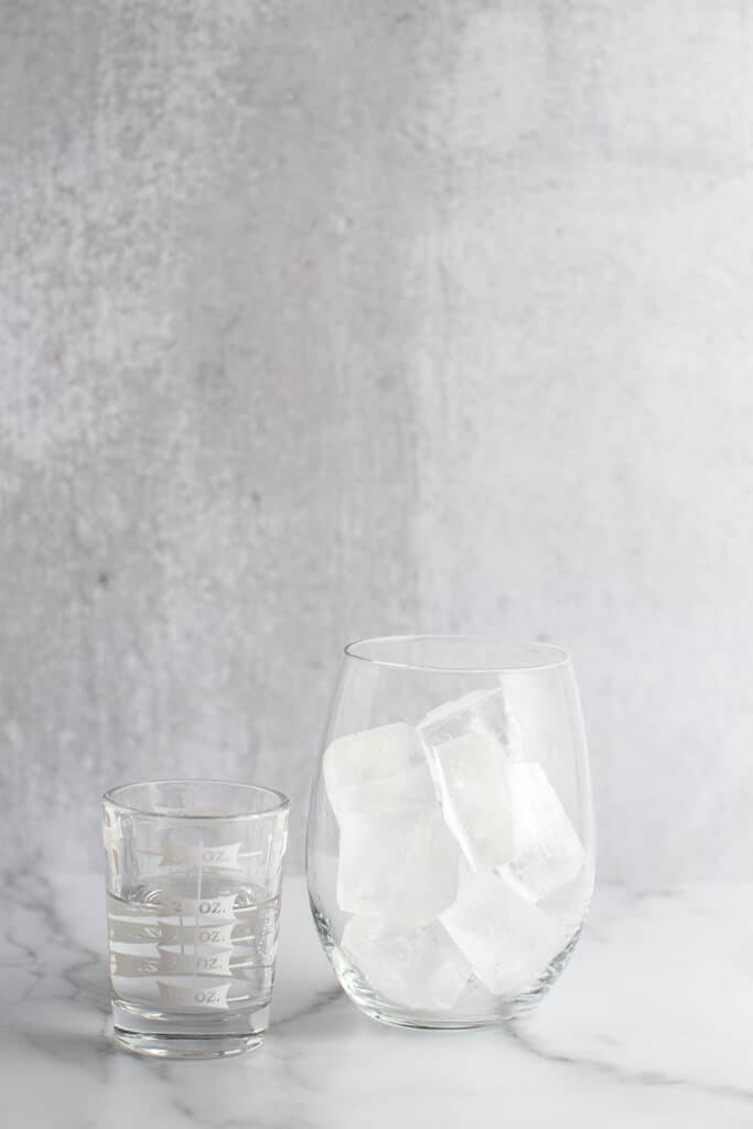 A glass shot glass with vodka next to a glass filled with ice