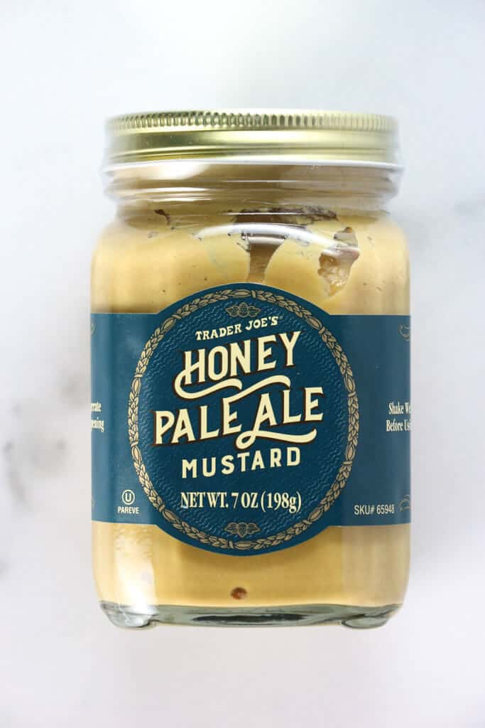 An unopened jar of Trader Joe's Honey Pale Ale Mustard on a marble background