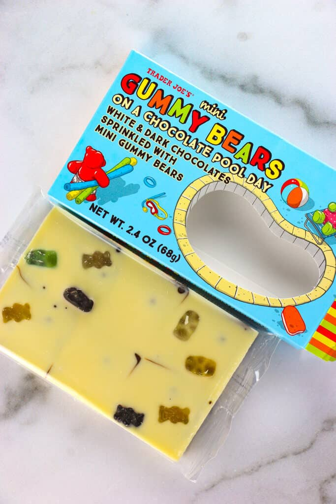 An opened box of Trader Joe's Mini Gummy Bears on a Chocolate Pool Day showing the white chocolate top with the gummy bears