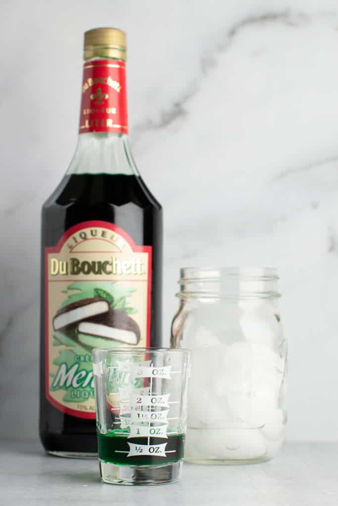 One ounce of creme de menthe next to the original bottle and cocktail shaker