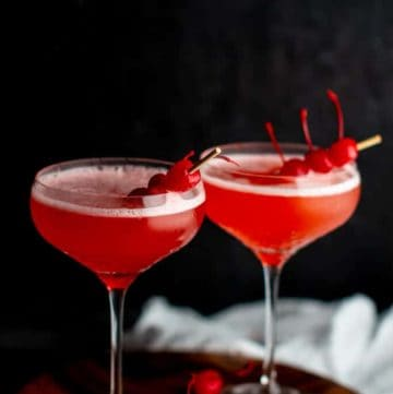 Two Mary Pickford Cocktails garnished with cherries