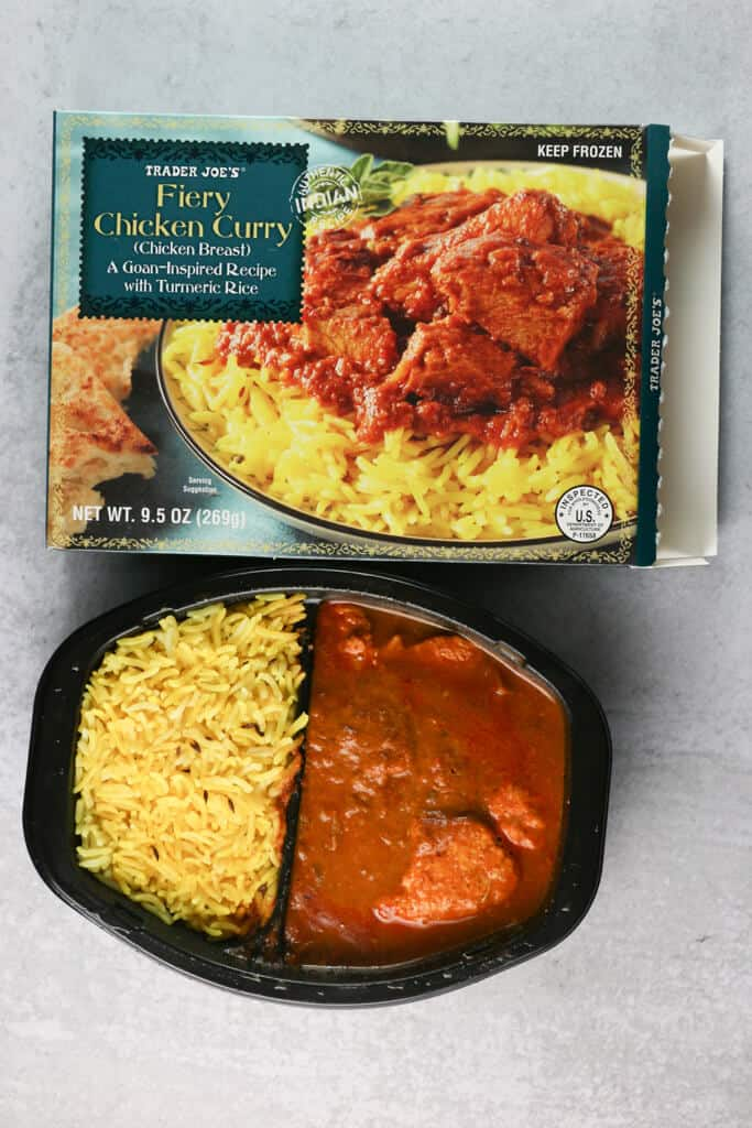 A fully cooked Trader Joe's Fiery Chicken Curry next to the original box