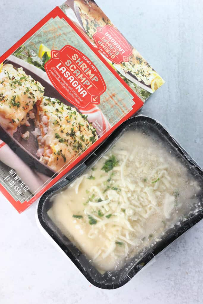 An open box of Trader Joe's Shrimp Scampi Lasagna showing the frozen entree
