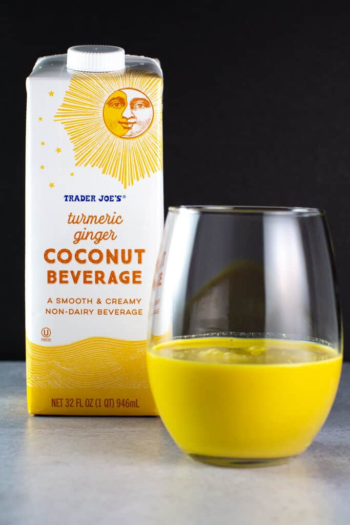 An opened package of Trader Joe's Turmeric Ginger Coconut Beverage poured into a glass showing off the yellow liquid