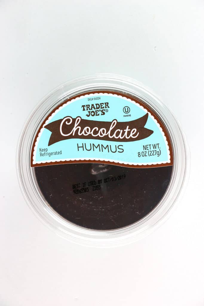 An unopened container of Trader Joe's Chocolate Hummus on a white surface