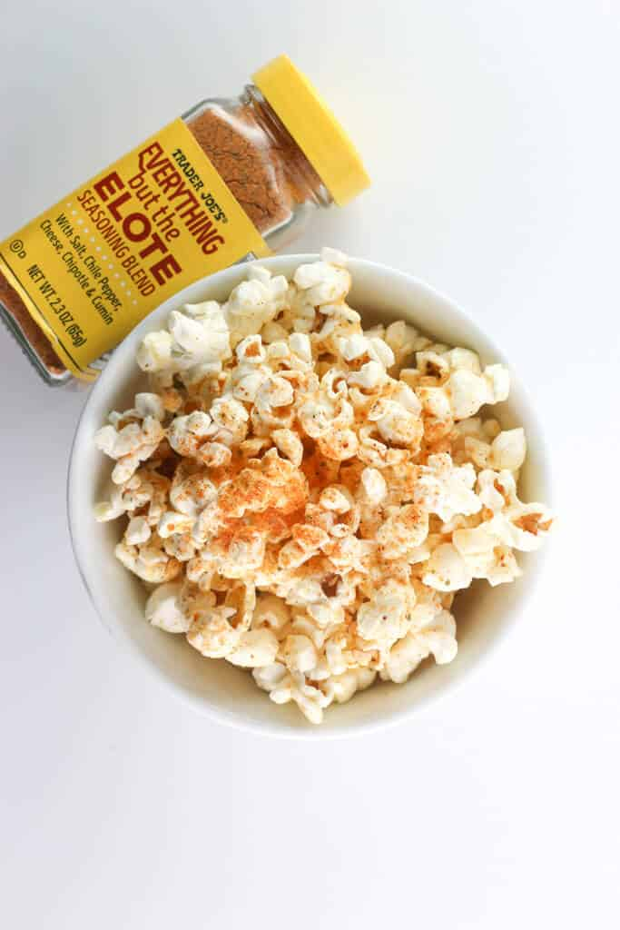 Some Trader Joe's Everything but the Elote Seasoning Blend sprinkled on some popcorn next to the original jar