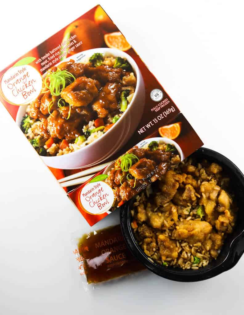 A fully heated Trader Joe's Mandarin Style Orange Chicken Bowl with the packet of sauce and original box next to the product.