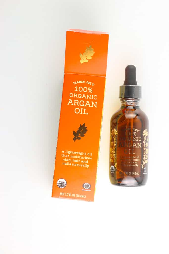 An open bottle of Trader Joe's 100% Organic Argan Oil next to the original box