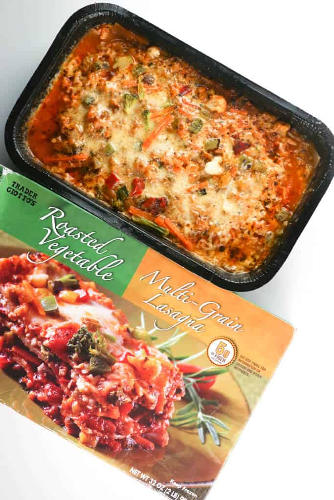 A fully cooked Trader Joe's Roasted Vegetable Multi-Grain Lasagna next to the original box