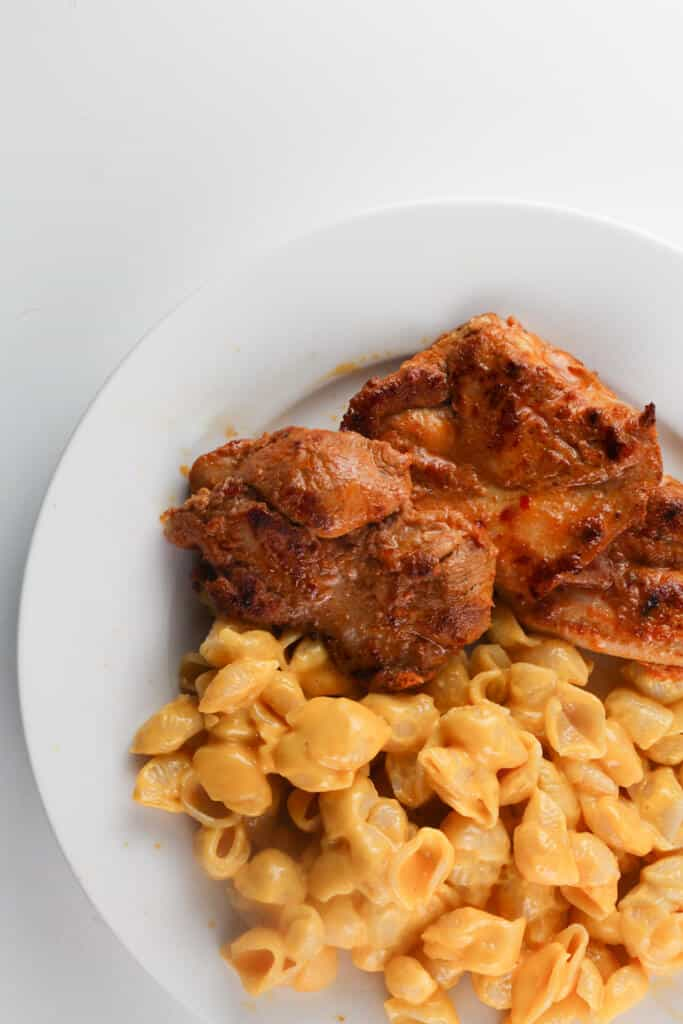 Fully cooked Trader Joe's Harissa Flavored Chicken Thighs o a plate with mac and cheese