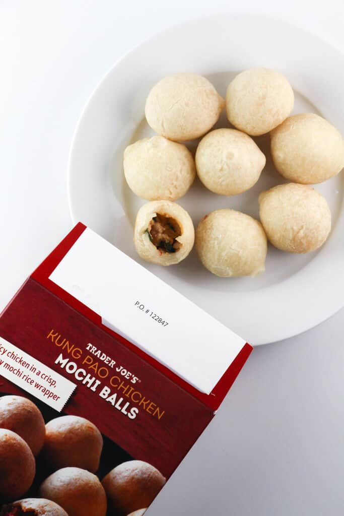 A fully cooked box of Trader Joe's Kung Pao Chicken Mochi Balls next to the original package