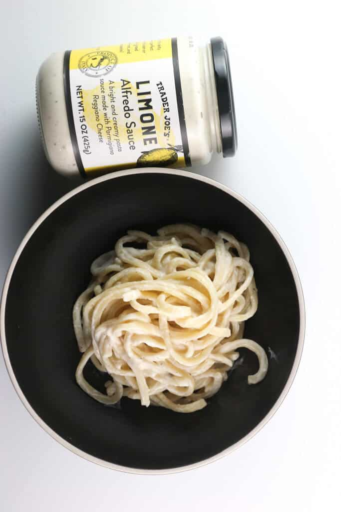 A black bowl with fettuccine in it next to a jar of Trader Joe's Limone Alfredo Sauce