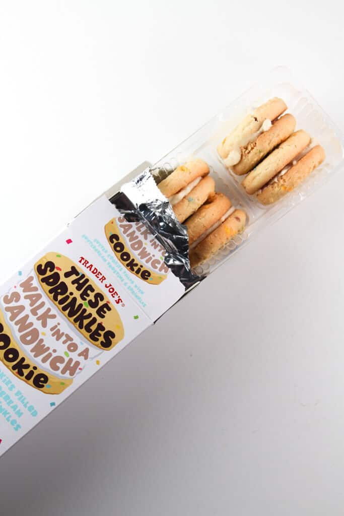 An open box of Trader Joe's These Sprinkles Walk Into a Sandwich Cookie showing the rows of cookie sandwiches