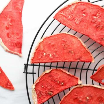 Dehydrated watermelon on a wire rack with two dried slices off to the side