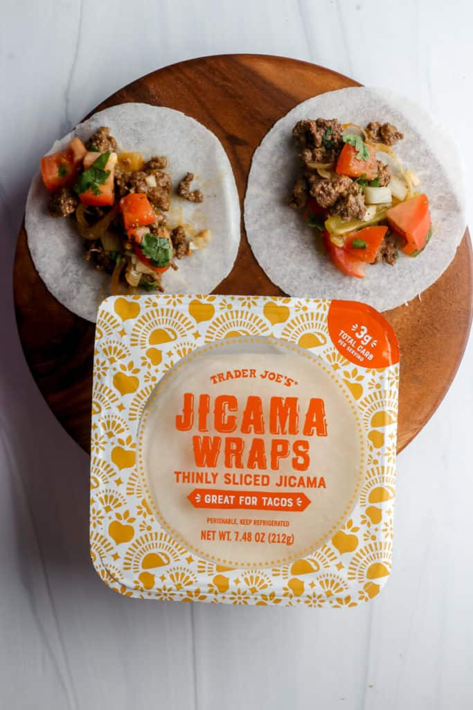 Two tacos next to the package of Trader Joe's Jicama Wraps