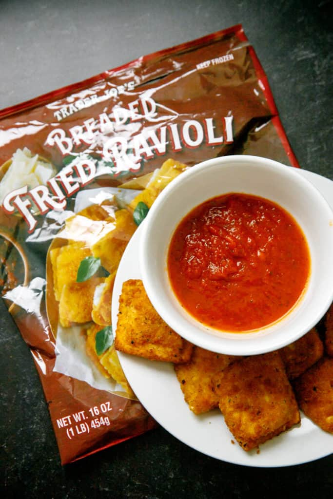 Fully heated Trader Joe's Breaded Fried Ravioli with sauce and the original bag next to the plate of food.