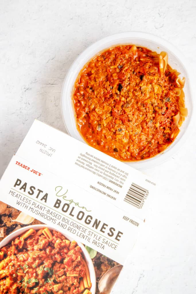 A fully cooked Trader Joe's Vegan Pasta Bolognese with the box next to it